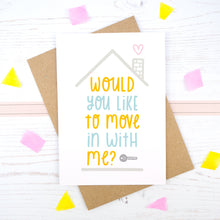 Would you like to move in with me card in blue and orange, under a grey roof and a dark grey key.
