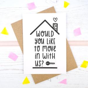Would you like to move in with us card in black & white, under a roof with a chimney and heart.