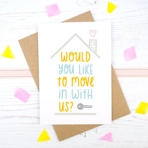 Would you like to move in with us card in blue and orange, under a grey roof and a dark grey key.