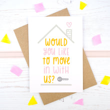 Would you like to move in with us card in pink and orange, under a grey roof and a dark grey key.