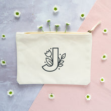 Load image into Gallery viewer, A natural cotton zipped pouch with a floral initial J printed in black.