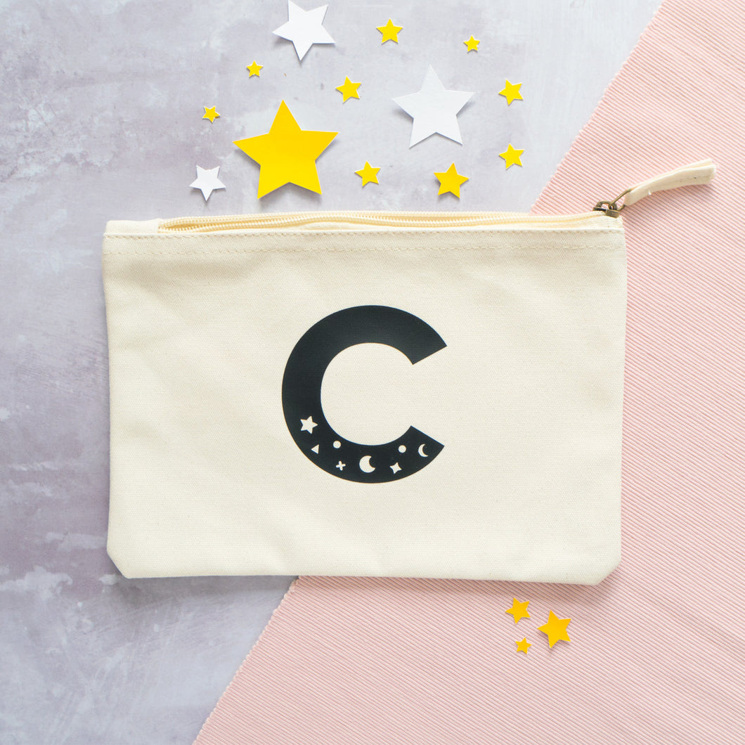 A natural cotton zipped pouch with a cosmic initial C printed in black.