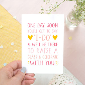 One day soon postponed wedding card in tones of pink. Photographed on a white, yellow and pink background with flowers poking in the top right hand side.