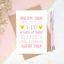 Load image into Gallery viewer, One day soon postponed wedding card in tones of pink. Photographed on a white and pink background with a hint of small flowers and a pen.