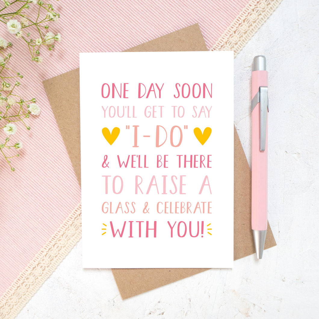 One day soon postponed wedding card in tones of pink. Photographed on a white and pink background with a hint of small flowers and a pen.