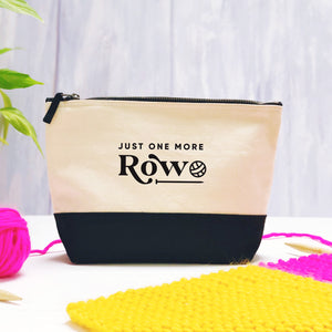 A 'just one more row' cotton storage bag, natural in colour with a black box bottom base photographed on a purple background with leaves, and a ball of pink wool with a knitting project.
