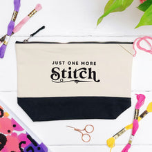 Load image into Gallery viewer, A just one more stitch cotton storage bag, natural in colour with a black box bottom base photographed in a flat lay style surrounded by cross stitch and threads.