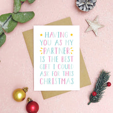 Load image into Gallery viewer, A best partner Christmas card as a flatlay on a pink background with foliage, baubles and festive decor. The card text is in pink and blue.
