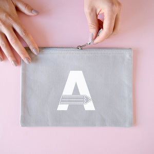 A grey cotton zipped pouch with a pencil initial A printed in white.