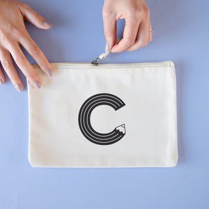 A natural cotton zipped pouch with a pencil initial C printed in black.