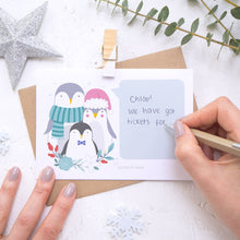 Load image into Gallery viewer, A personalised penguin family scratch card showing where to write the hand written message. Shot on a white background with grey and green festive props and a glittery star.