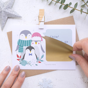 A personalised penguin family scratch card where the sticking down of the gold scratch panel is being demonstrated. Shot on a white background with a glittery star and sprig of eucalyptus.