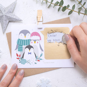 A personalised penguin family scratch card where the scratching off of the gold panel is being demonstrated. Shot on a white background with a glittery star and sprig of eucalyptus.