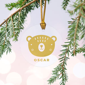 A personalised gold bear Christmas bauble decoration made from clear acrylic and hung on gold hanging cord from a Christmas tree.