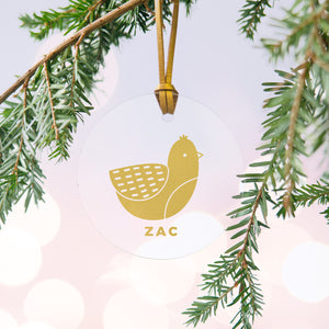 A personalised gold bird Christmas bauble decoration made from clear acrylic and hung on gold hanging cord from a Christmas tree.