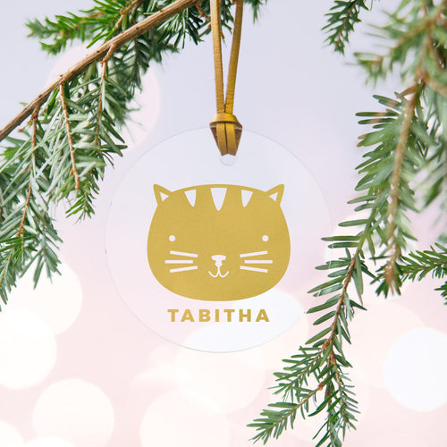 A personalised gold cat Christmas bauble decoration made from clear acrylic and hung on gold hanging cord from a Christmas tree.