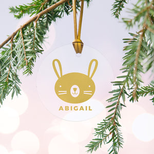 A personalised gold rabbit Christmas bauble decoration made from clear acrylic and hung on gold hanging cord from a Christmas tree.