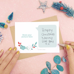 A draw your own scratch card showing where to hand write the message for scratching off. Shot on pink with snow and greenery.