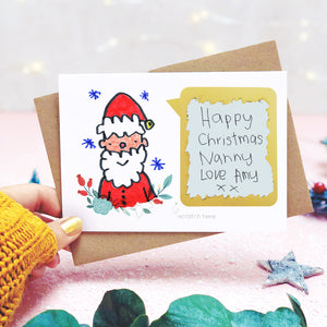 A make your own Christmas scratch card showing a childs drawing of father christmas and the scratch panel having been scratched to reveal the hand written message. Shot on pink and white with a hand and greenery.