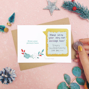 A make your own scratch card where the scratch off message has been revealed. Shot on pink with snow and greenery.