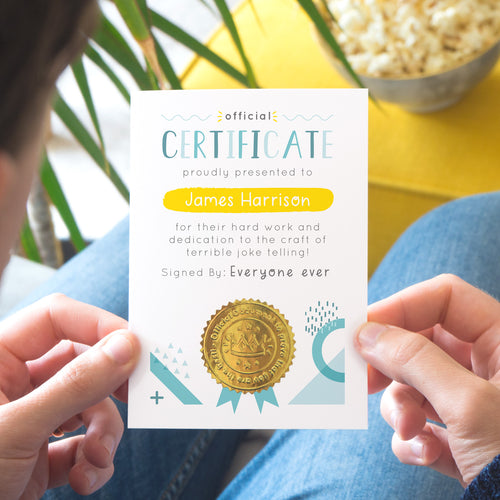 A personalised fathers day certificate printed on white card with varying tones of blue and pops of yellow and gold. Each certificate has a shiny gold seal and space to sign your name. Photographed over a lap with a yellow foot rest in the background.