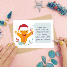 Load image into Gallery viewer, A personalised Gingerbread man scratch card showing where to write the hand written message. Shot on a pink background with grey and green festive props.