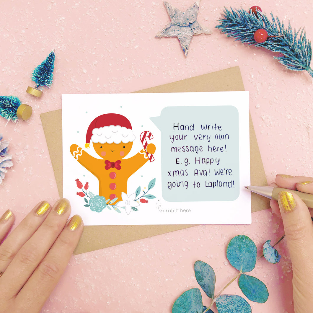 A personalised Gingerbread man scratch card showing where to write the hand written message. Shot on a pink background with grey and green festive props.