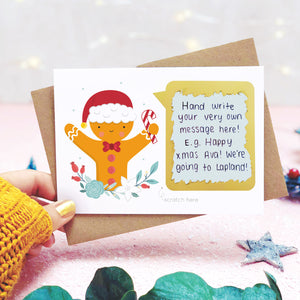 A personalised gingerbread man scratch card shot in a lifestyle setting with a pink background being held behind a sprig of eucalyptus and festive props. The scratch panel has been scratched off to reveal the hidden message.