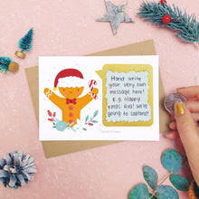 Load image into Gallery viewer, A personalised gingerbread man scratch card after the gold panel has been attached.Shot on a pink background with grey and green festive props.