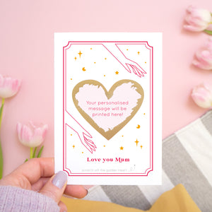A personalised 'love you...' scratch card with the gold heart scratched off revealing where the personalised message will be printed. The card is photographed held over a pink background with tulips!