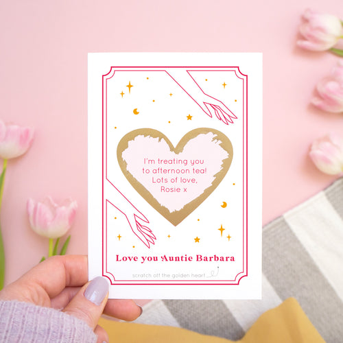 A personalised 'love you...' scratch card with the gold heart scratched off revealing the personalised message. The card is photographed held over a pink background with tulips!