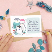 Load image into Gallery viewer, A personalised penguin family scratch card showing where to write the hand written message. Shot on a pink background with grey and green festive props.