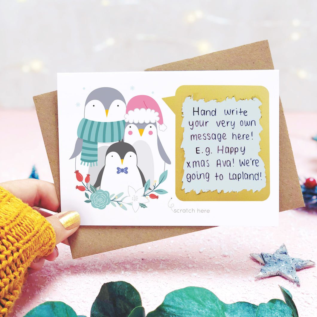 A personalised penguin family scratch card shot in a lifestyle setting with a pink background being held behind a sprig of eucalyptus and festive props. The scratch panel has been scratched off to reveal the hidden message.