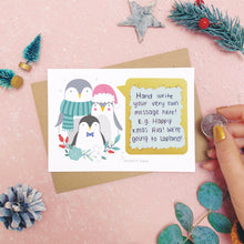 Load image into Gallery viewer, A personalised penguin family scratch card after the scratch panel has been scratched with a coin to reveal the hidden message.Shot on a pink background with grey and green festive props.