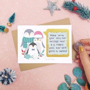A personalised penguin family scratch card after the scratch panel has been scratched with a coin to reveal the hidden message.Shot on a pink background with grey and green festive props.