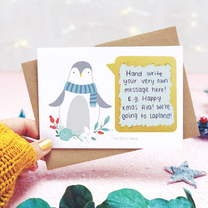 Personalised penguin scratch card shot on a light pink background behind eucalyptus with the scratch off message revealed.