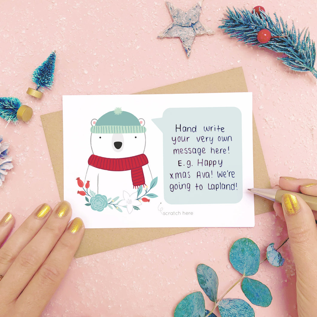 A personalised polar bear scratch card shot on a pink background with festive props in grey and green. This is an example of where to write your hidden message.