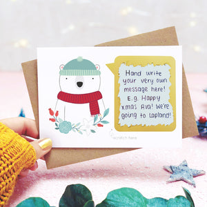 A personalised polar bear scratch card with the hand written message revealed. Shot on a pink background, behind a sprig of eucalyptus and festive props.