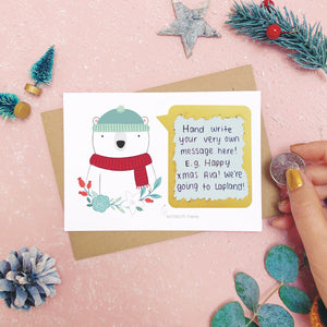 A personalised polar bear scratch card shot on a pink background with festive props in grey and green. The scratch panel has been scratched off with a coin to reveal the hidden message.