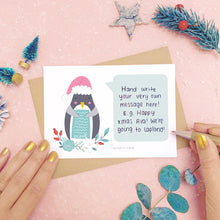 Load image into Gallery viewer, Santa Penguin scratch card showing where you write your hidden message. Shot on a pink background, surrounded with festive christmas props in tones of green and grey.