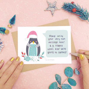 Santa Penguin scratch card showing where you write your hidden message. Shot on a pink background, surrounded with festive christmas props in tones of green and grey.
