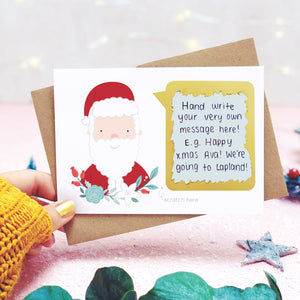 A personalised santa scratch card being held behind eucalyptus leaves, on a pink background with the scratch off message revealed