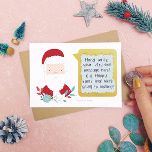 An example of a handwritten message on a personalised scratch card after it has been scratched off with a coin.. Shot on a pink background with festive photo props.