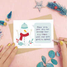 Load image into Gallery viewer, A personalised snowman scratch card showing where to write the hand written message. Shot on a pink background with grey and green festive props.