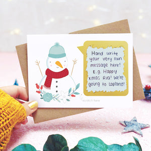 A personalised snowman scratch card shot in a lifestyle setting with a pink background being held behind a sprig of eucalyptus and festive props. The scratch panel has been scratched off to reveal the hidden message.