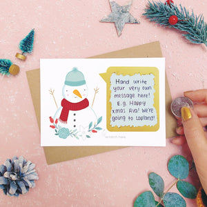 A personalised snowman scratch card after the scratch panel has been scratched with a coin to reveal the hidden message.Shot on a pink background with grey and green festive props.