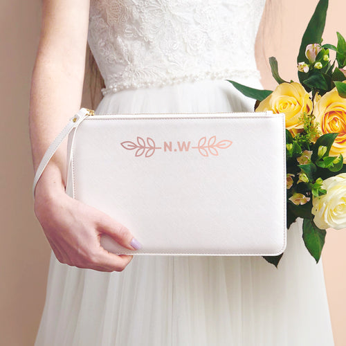 A white, personalised wedding wristlet held by Joanne Hawker in an ivory wedding dress with a bunch of peach and cream roses.