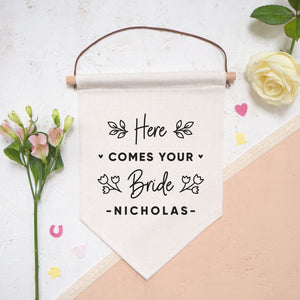A linen pennant flag with the words 'here comes your bride [insert name of groom]. Each flag features leafy vines and little hearts. This flag has been photographed on a white and peach background with confetti and flowers either side.