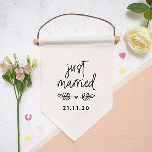 Just married personalised pennant flag with script 'just married', vine and a heart detail and a personalised wedding date. The flag is photographed on a white and peach background with confetti and flowers.