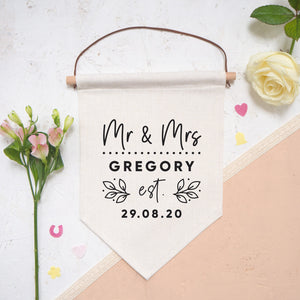 A personalised wedding pennant flag featuring your new title e.g. Mr & Mrs, your new family name and the date that you tied the knot. Photographed on a white and peach background with confetti and flowers either side of the flag.